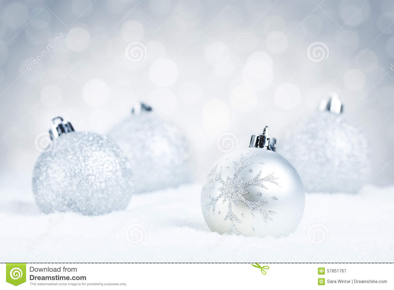 Silver christmas baubles on snow with a silver background for White christmas baubles