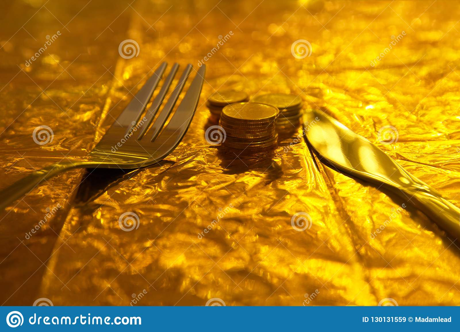 Silver fork and knife with coin money on gold background concept