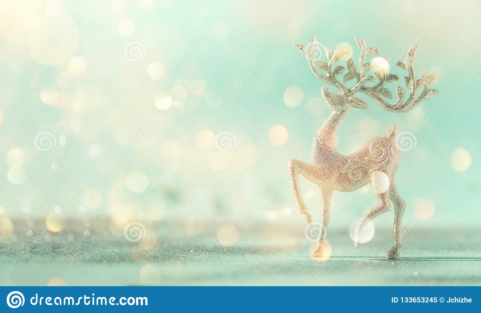 Silver glitter Christmas deer on blue background with lights bokeh, copy space. Greeting card for new year party. Festive holiday