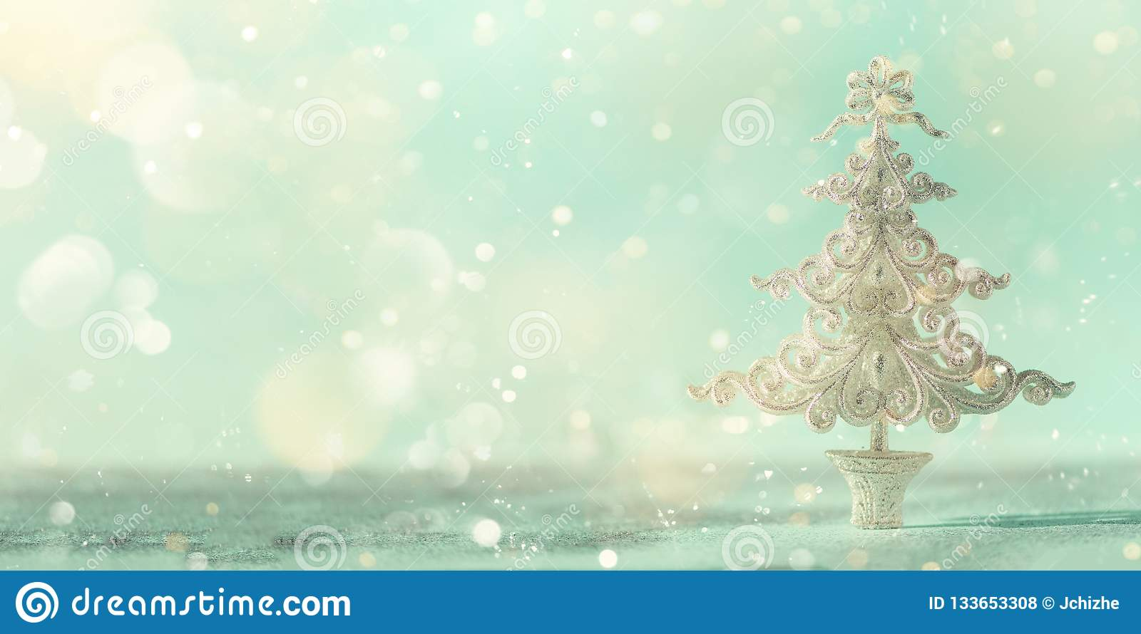 Silver glitter Christmas tree on blue background with lights bokeh, copy space. Greeting card for new year party. Festive holiday