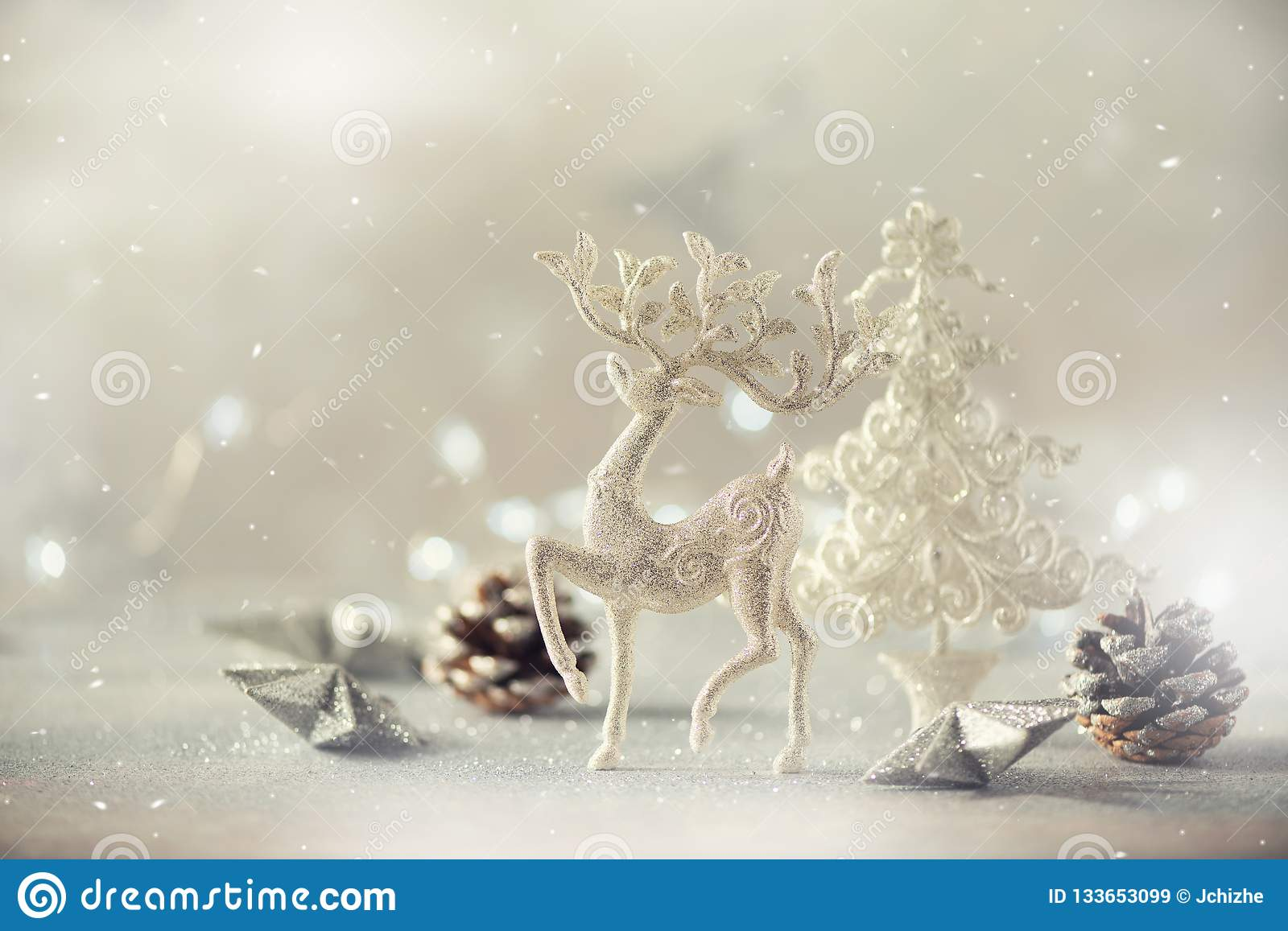 Silver glitter Christmas tree, deer, cones on grey background with lights bokeh, copy space. Greeting card for new year party.