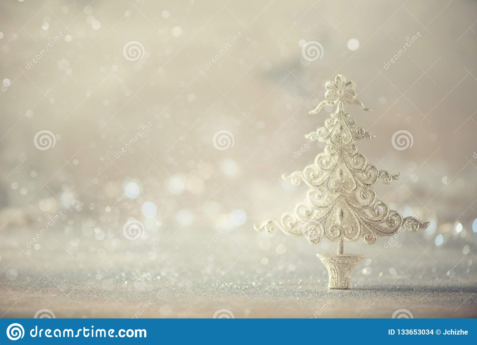 Silver glitter Christmas tree on grey background with lights bokeh, copy space. Greeting card for new year party. Festive holiday