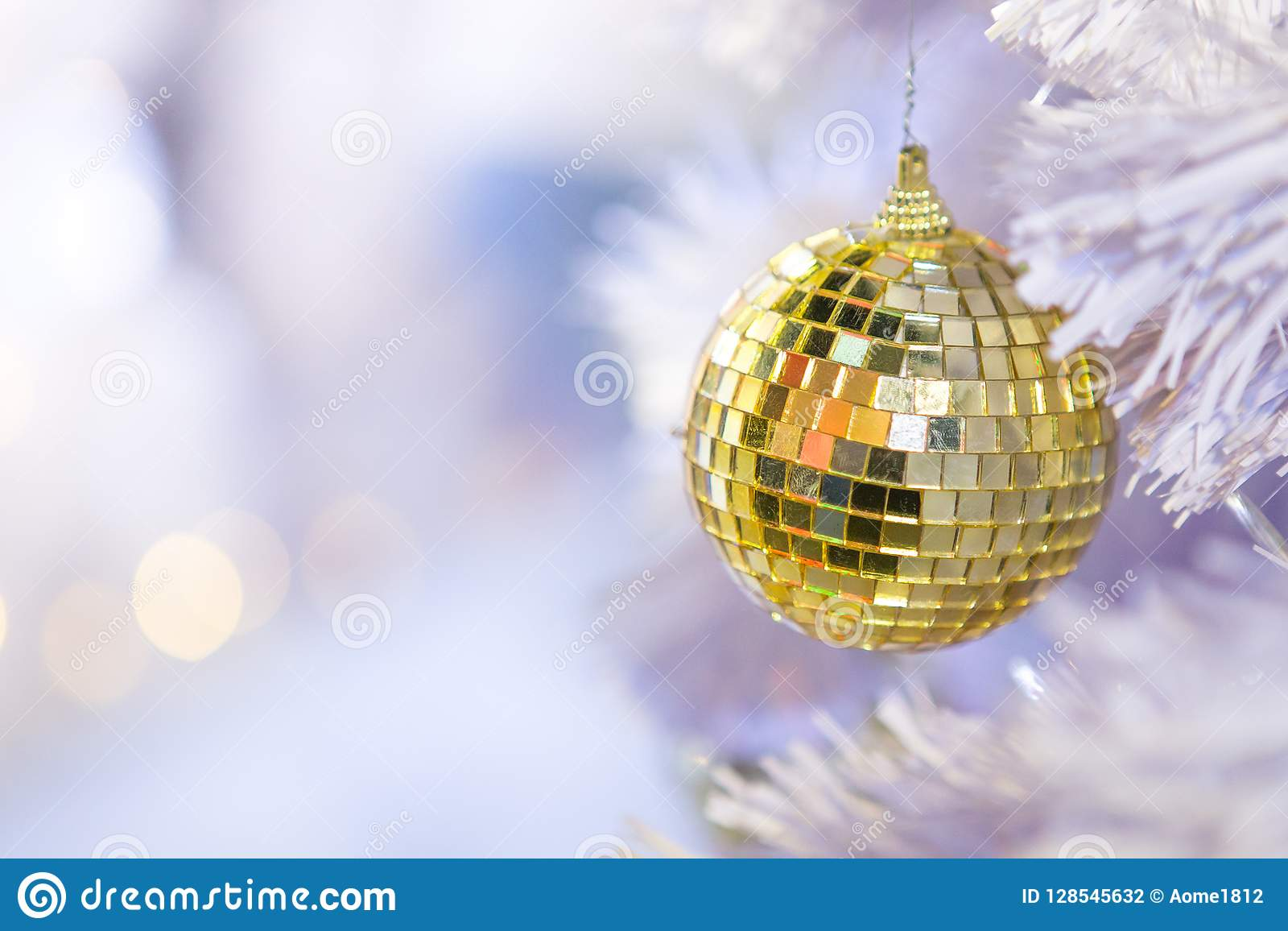 Silver and gold mirror balls on a white Christmas tree