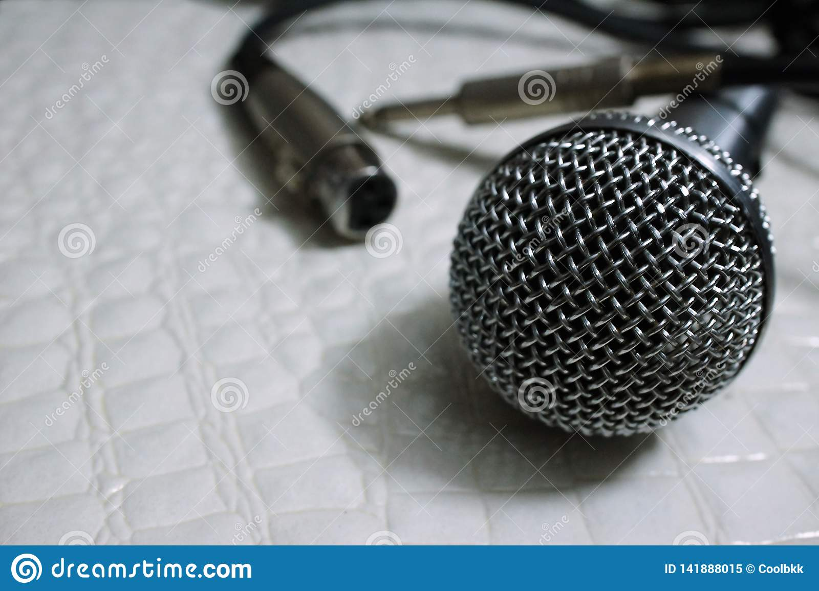 Silver Grille microphone with XLR cable on white leather SELECTIVE FOCUS