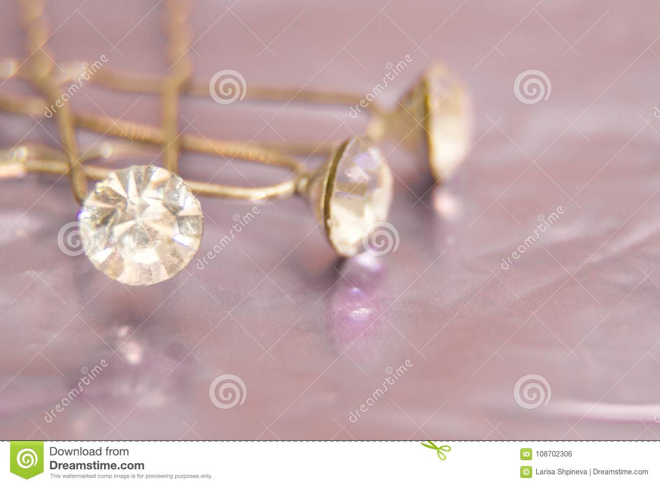 Beautiful hairpin decorated white diamonds for hairstyle on pink abstract bokeh background, hair accessories or wedding