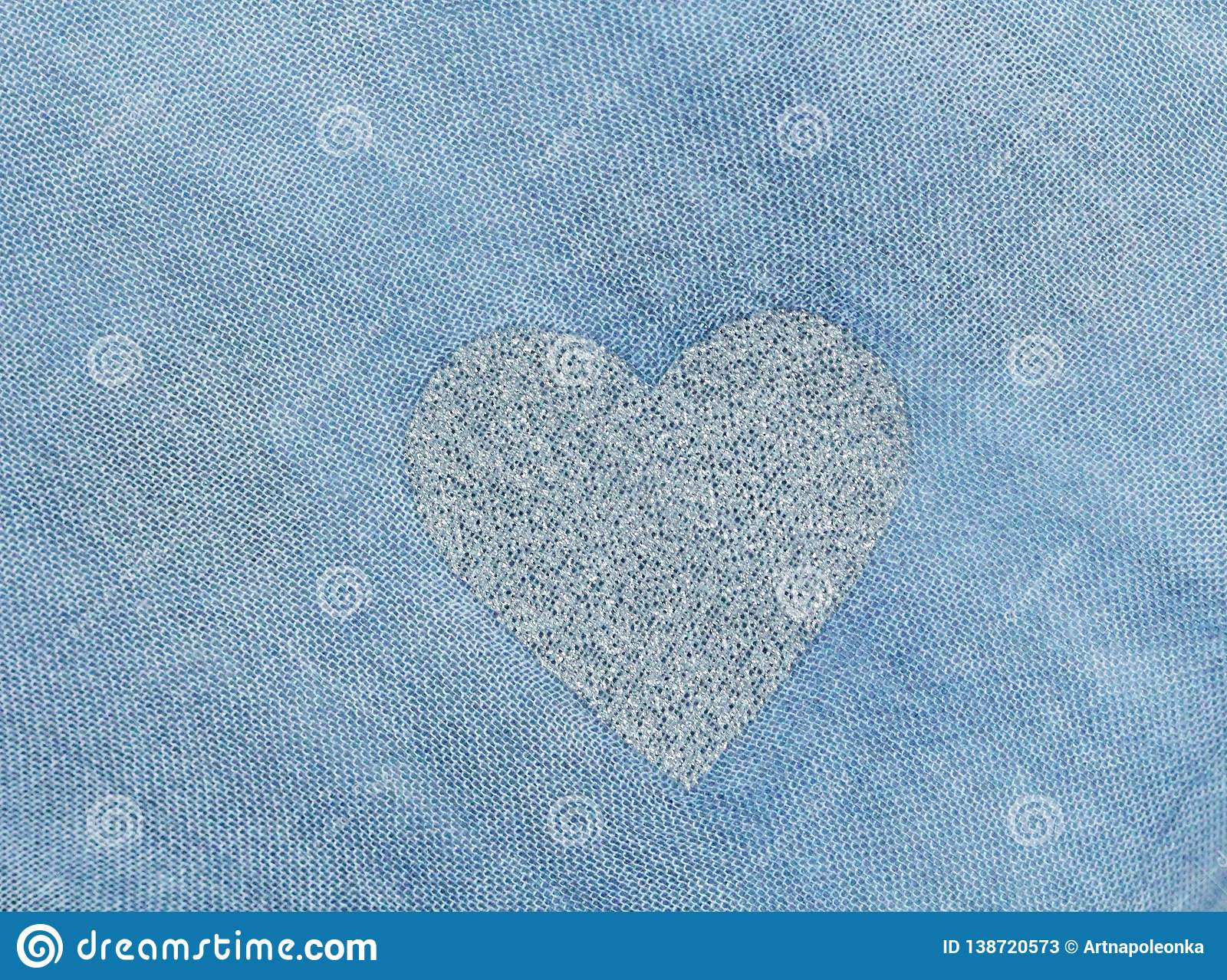 Silver heart on a blue background of cotton fabric. Romantic pastel background. Design with copy space. Denim color