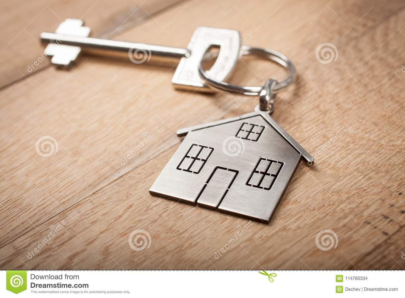 Close up silver home shaped keychain with key on wooden background. Mortgage, investment, real estate, property and new home conce
