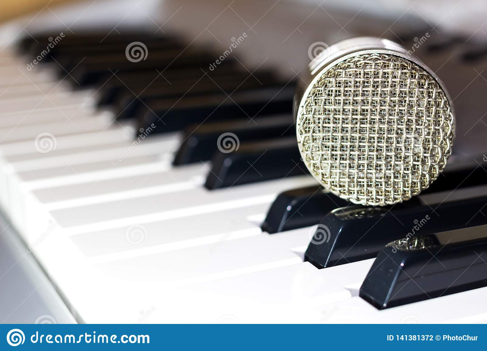 Silver microphone on the keyboard synthesizer