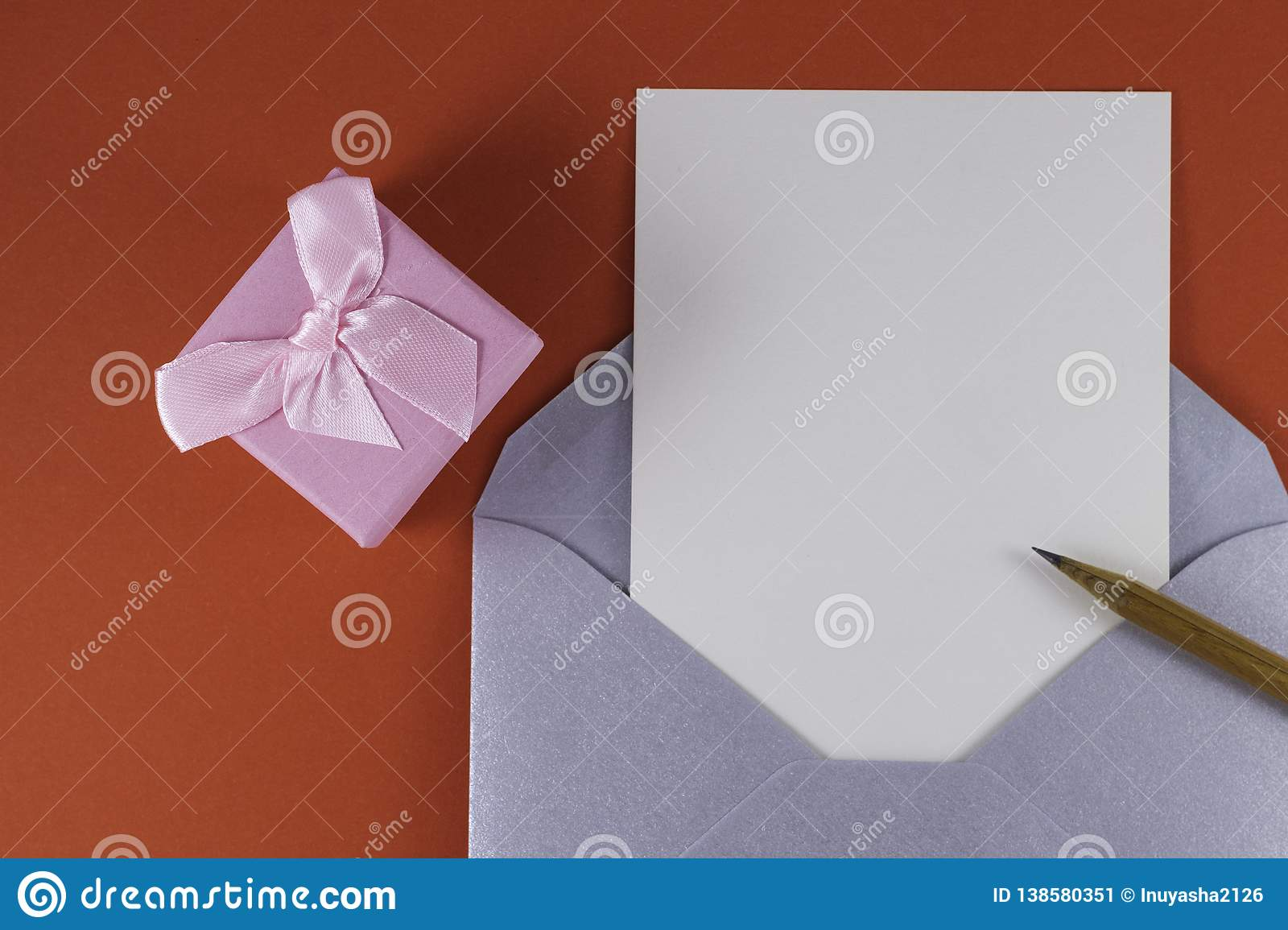 Silver open envelope with white blank letter inside Wooden pencil near and small pink gift box on a red background