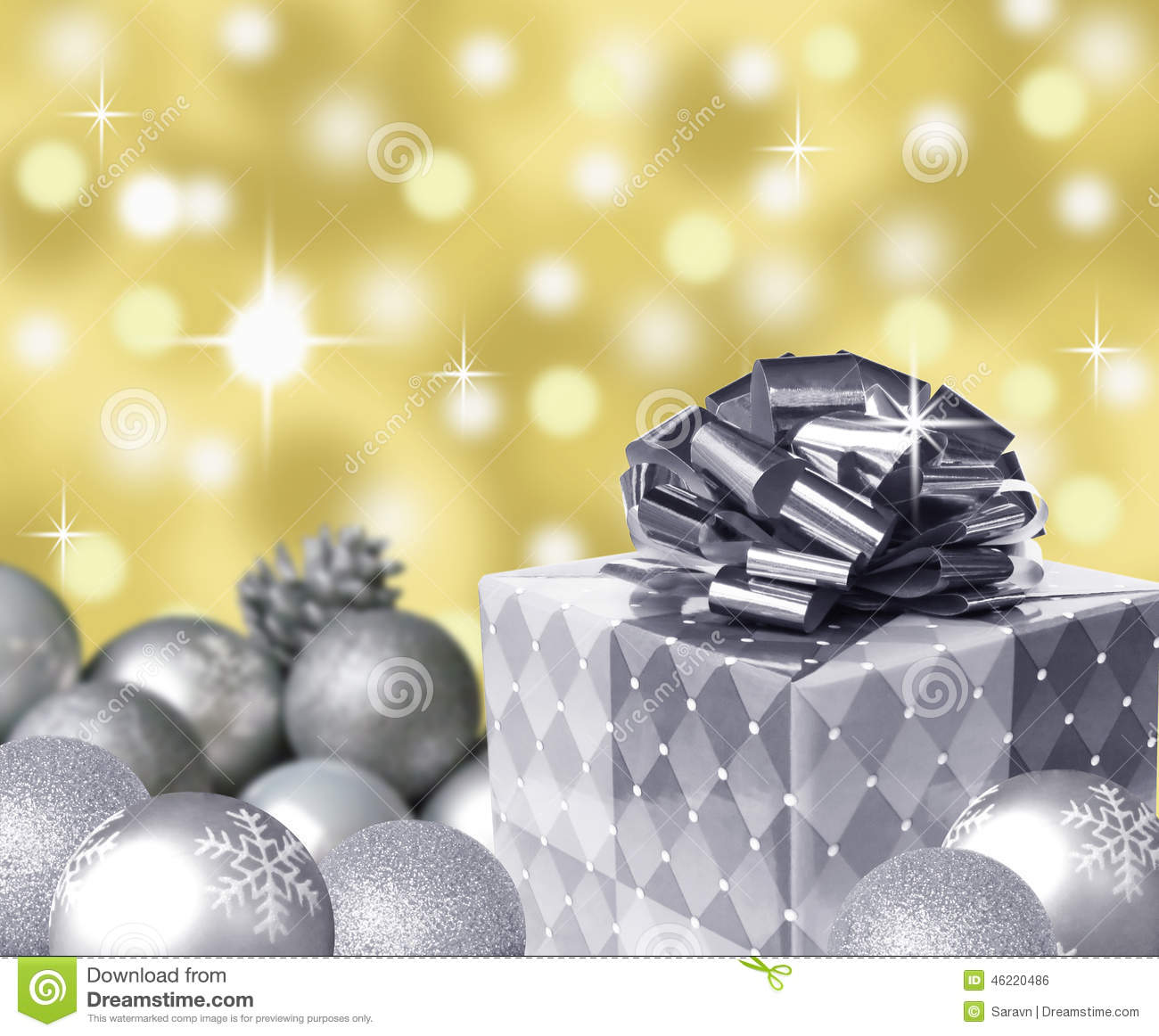 Silver present bow and christmas balls with snowflakes and gold abstract bokeh background