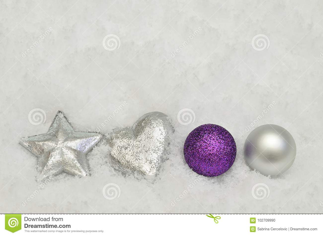 silver and purple christmas tree decorations on snow background