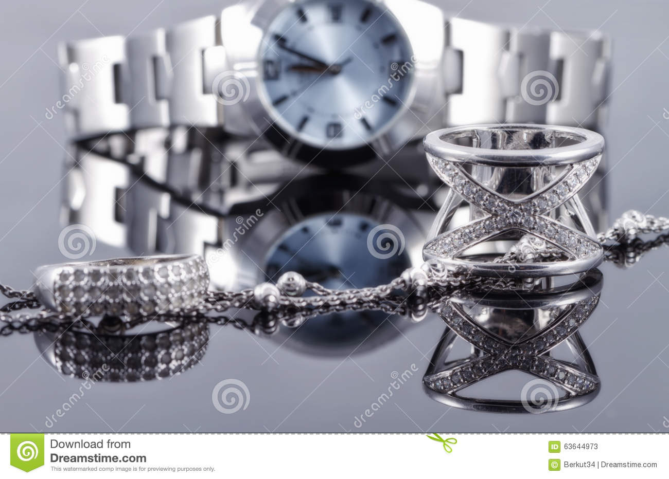 Silver rings and silver chain on the background of women s watch