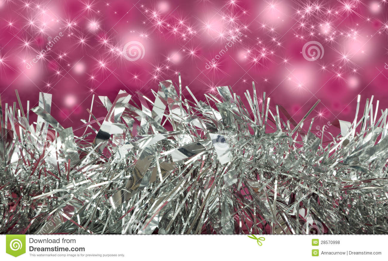 Silver tinsel garland with pink sparkle background stock