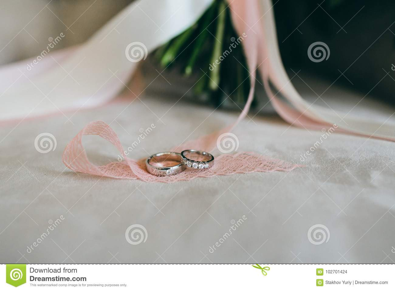 Silver wedding rings with gems on the piece of the ribbon. Close-up. Artwork