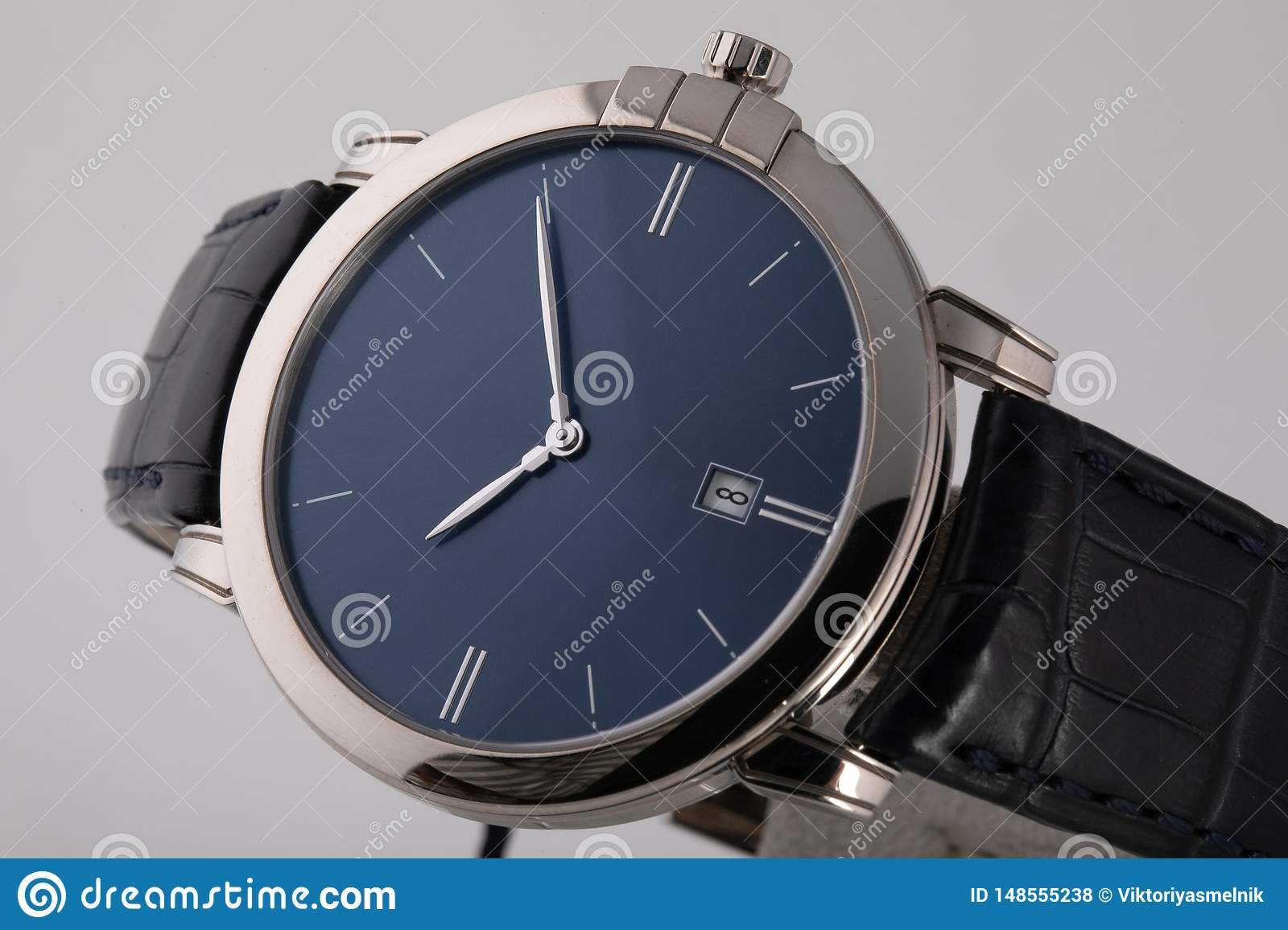 Silver wristwatch with blue dial, silver clockwise, chronograph on black leather strap on white background