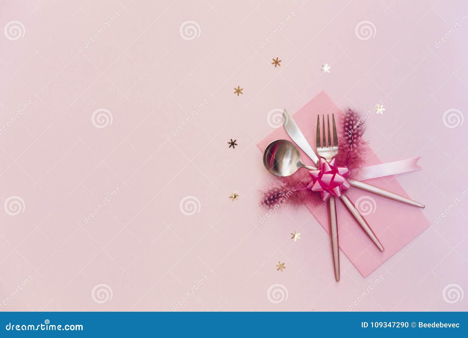 Silverware партии взгляд сверху Нож и ложка вилки над розовой предпосылкой