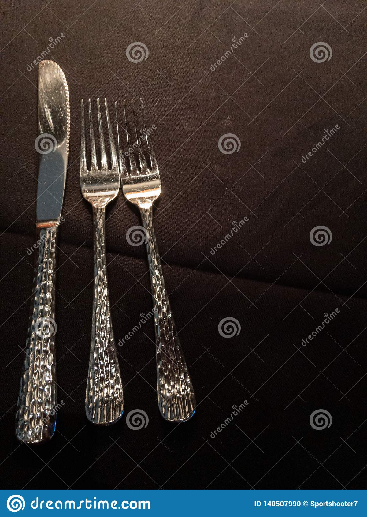 Silverware placement against black background.
