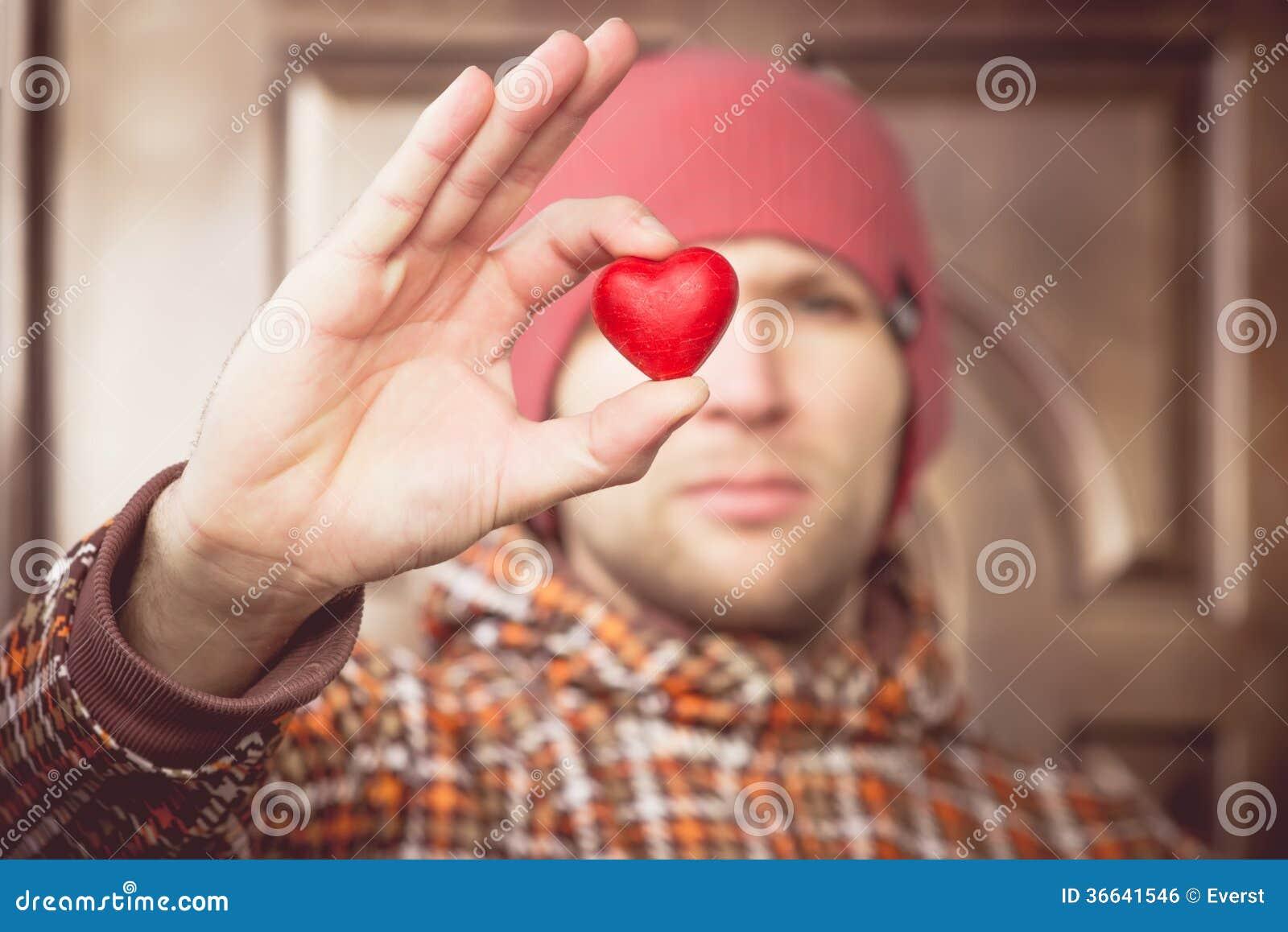 Simbolo di amore di forma del cuore in mano dell uomo con il fronte sul saluto romantico di giorno di biglietti di S. Valentino de