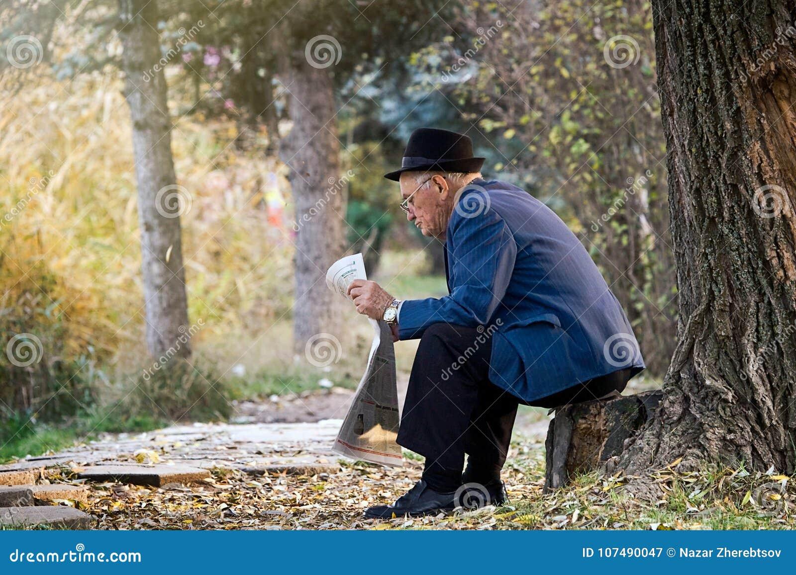 SIMFEROPOL, UKRAINE, November, 12,2009 - älterer Herr mit dem Hut, der auf dem Stumpf sitzt und eine Zeitung in einem Park liest