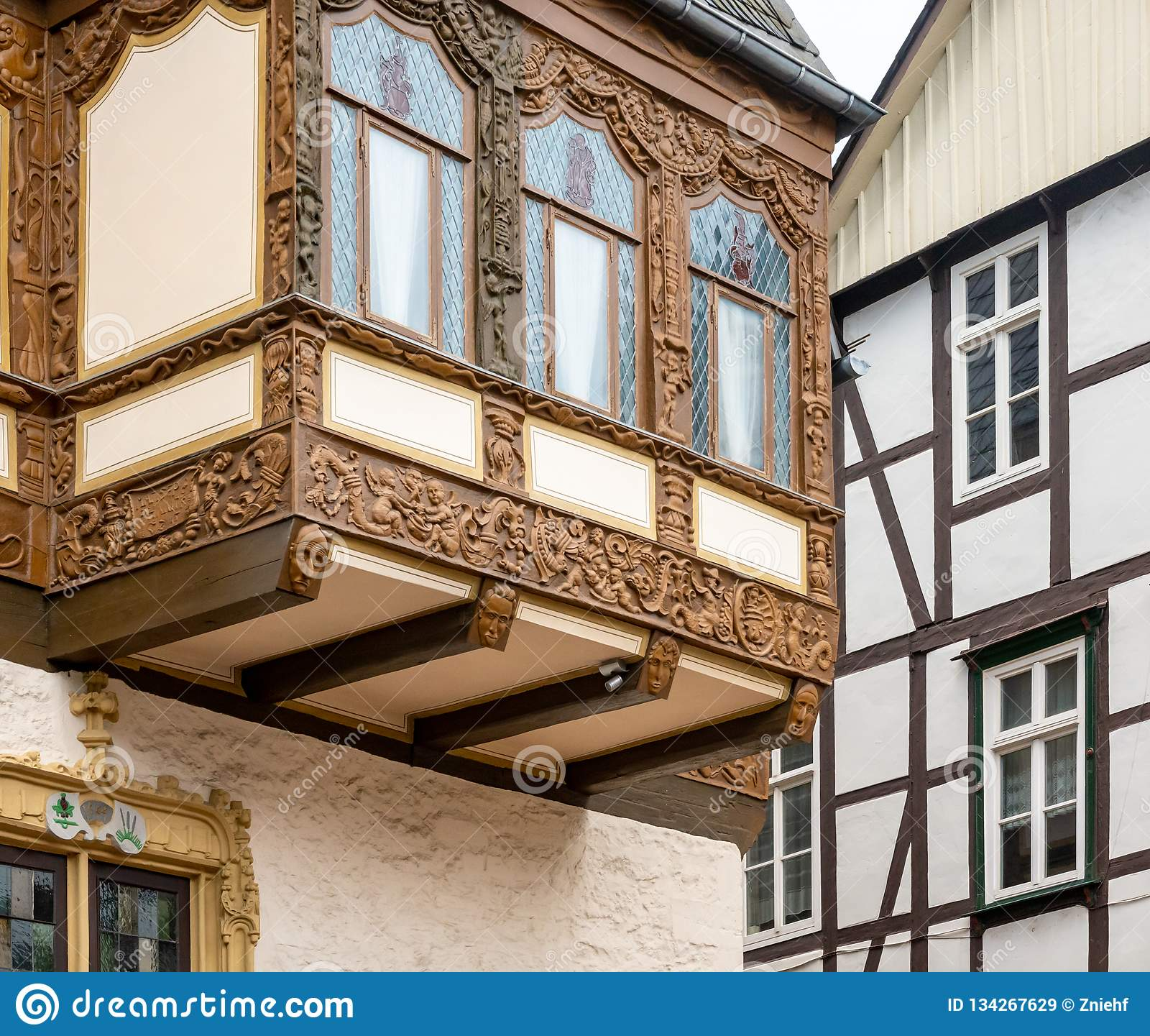 Simple half-timbered façade in the background and richly carved half-timbered house on an oriel in the old town