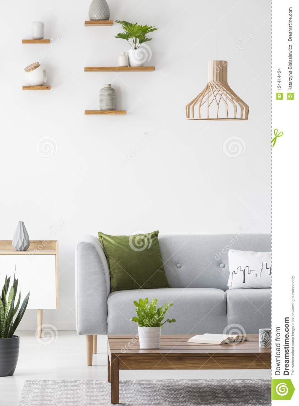 Simple shelves with vases on a white wall and wooden, scandinavian furniture in a bright living room interior with gray decor