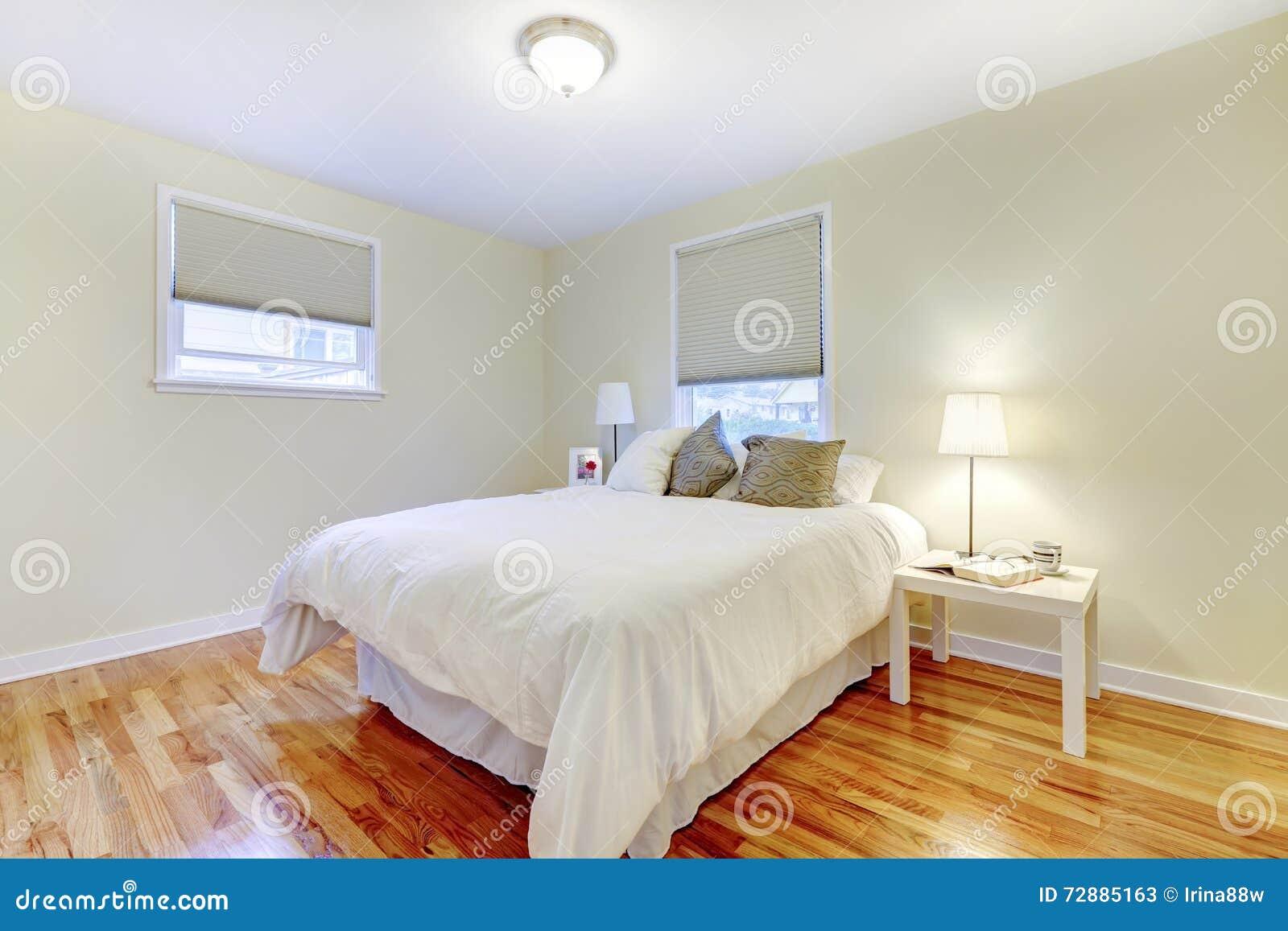 Simplistisch wit en bruin slaapkamerbinnenland met hardhoutvloer ...