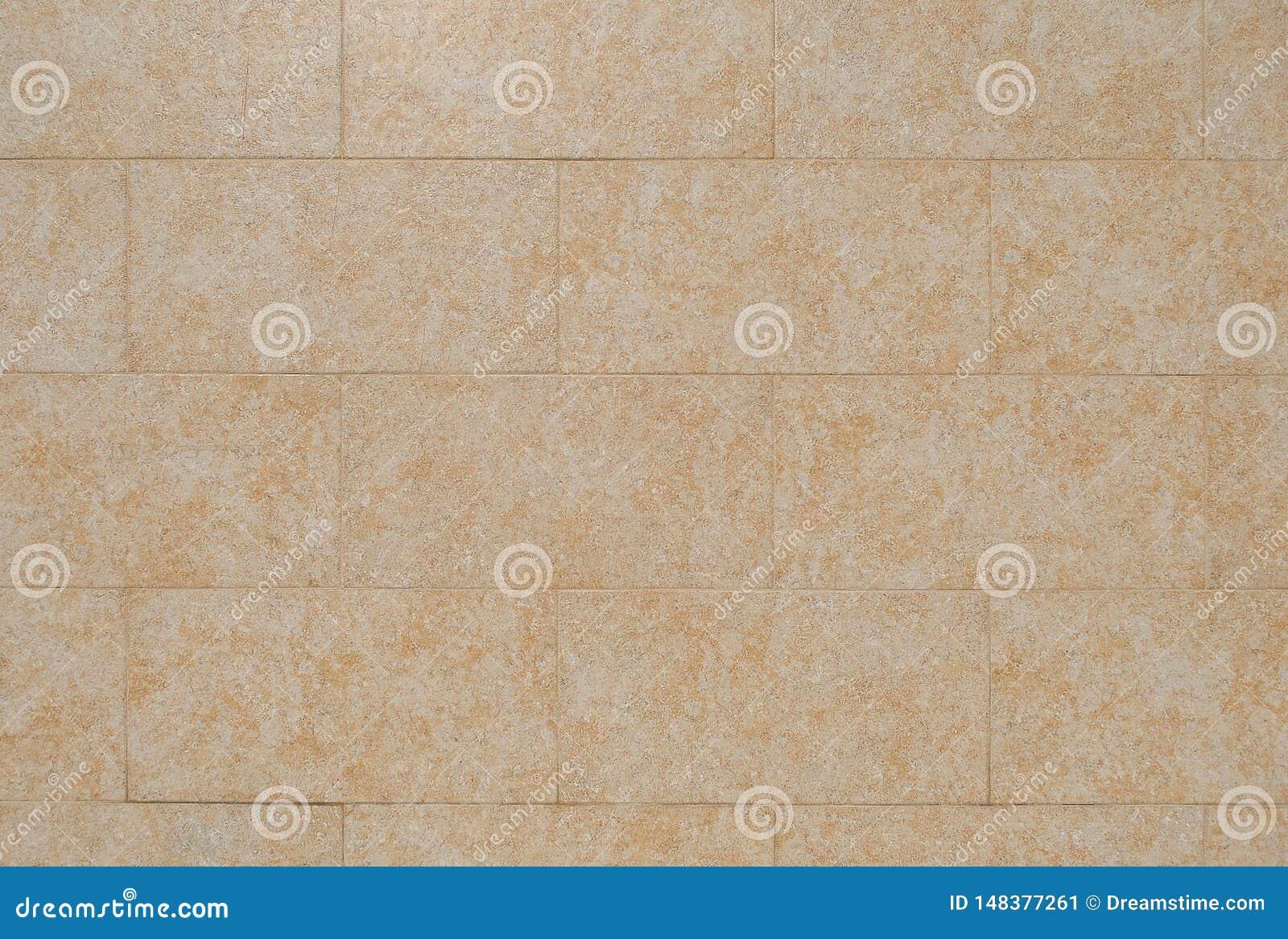 Sinaasappel die tegels onder ogen zien die van steen op de muur van het gebouw worden gemaakt