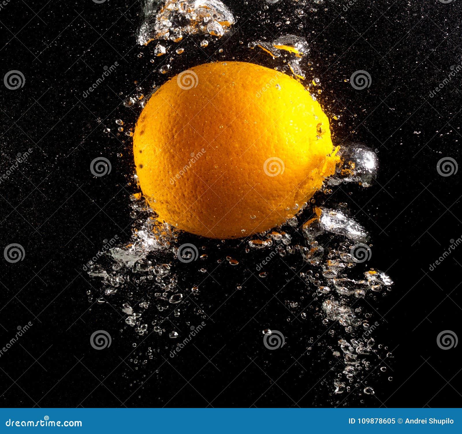 Sinaasappel onder water op een zwarte achtergrond