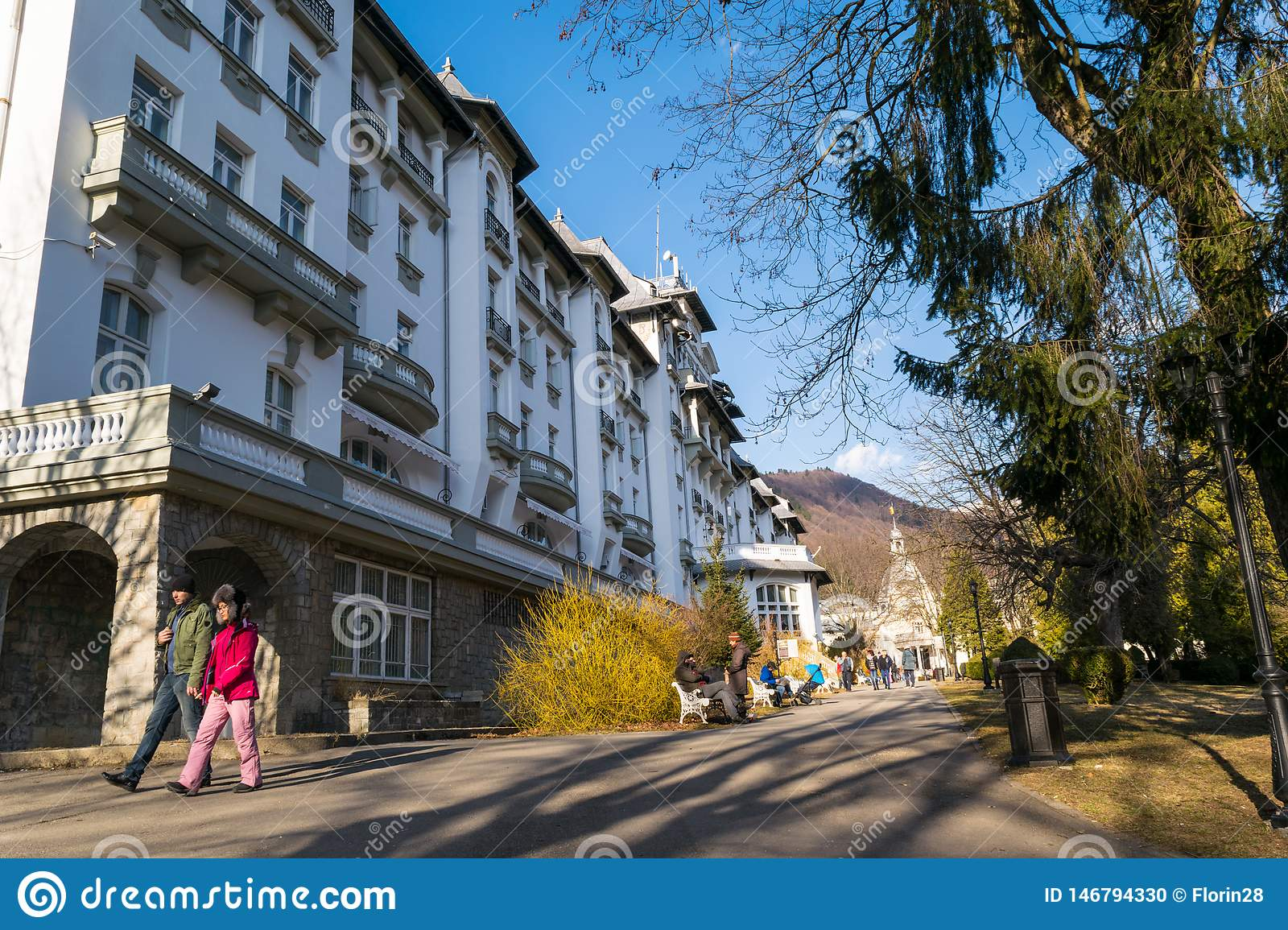Sinaia, Romania - March 09, 2019: People enjoy an walk in Sinaia`s central Park alleys along side Palace Hotel in Prahova county,
