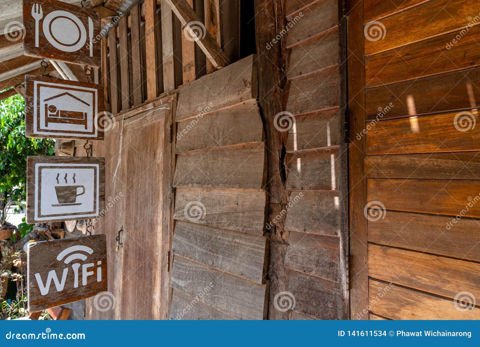 Sinais que penduram na frente de uma estada de madeira velha da casa