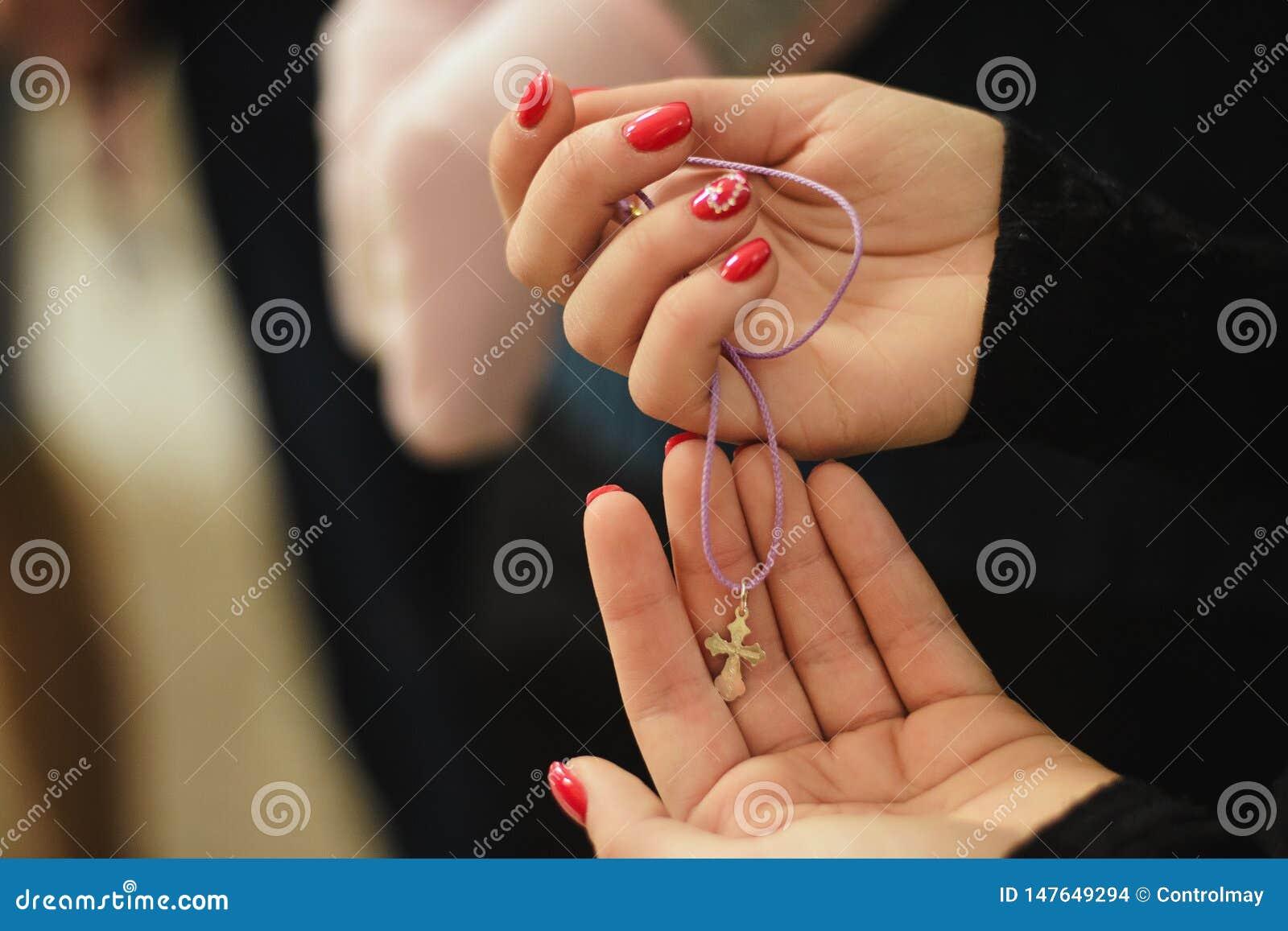 Sinal da religião nas mãos de uma menina