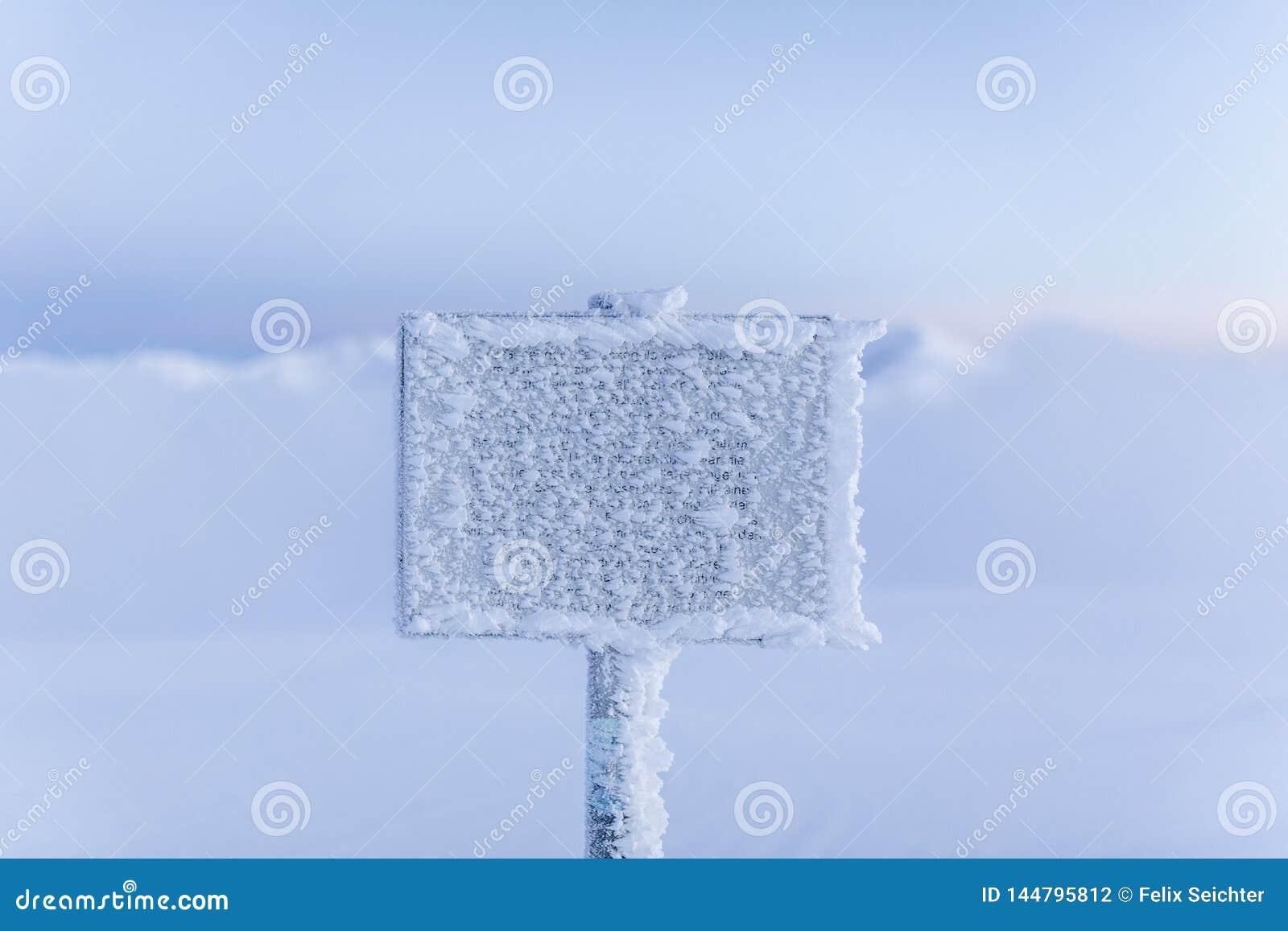 Sinal de aviso congelado na montanha nevoenta no tempo de inverno