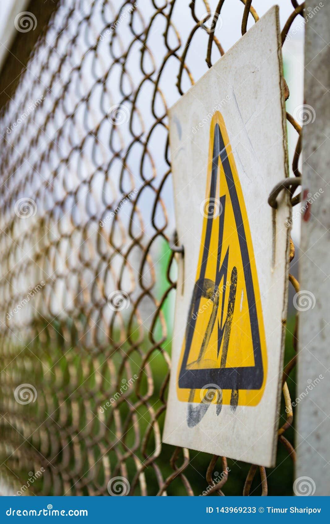 Sinal de aviso em uma cerca do ferro