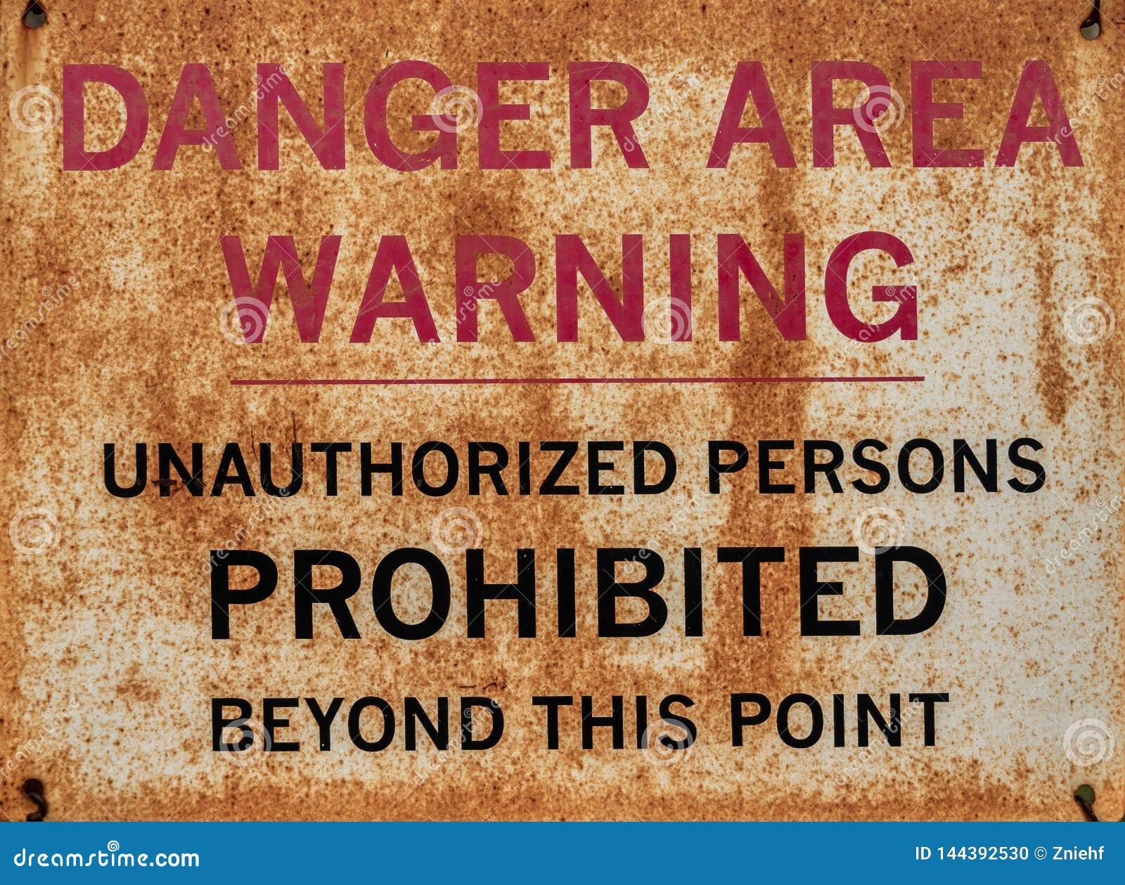 Sinal de aviso oxidado com a inscrição: Zona de perigo, aviso, pessoas desautorizadas proibidas além deste ponto