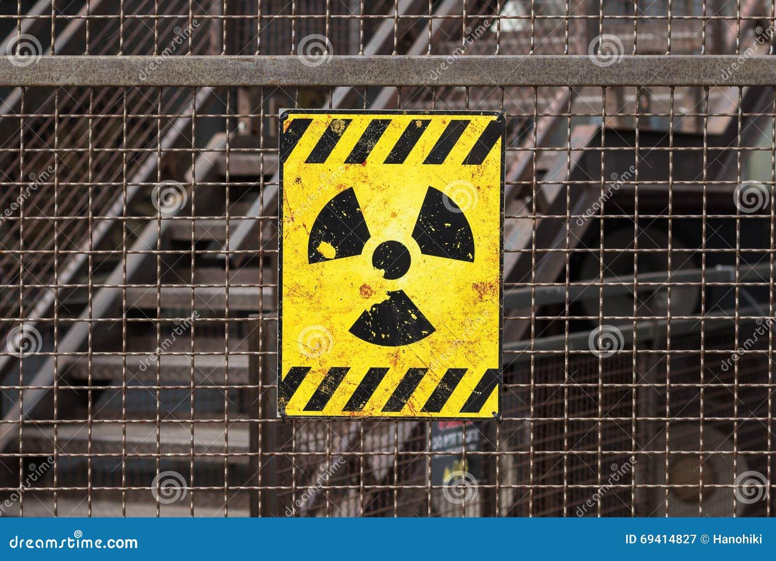 Sinal de aviso radioativo na cerca oxidada