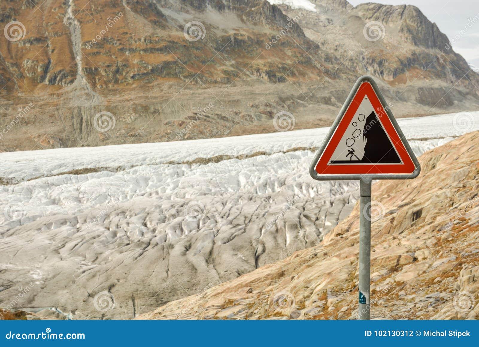 Sinal de estrada com aviso contra rochas de queda