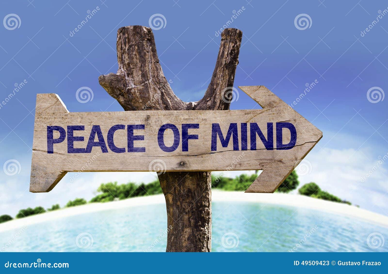 Sinal de madeira da paz de espírito com uma praia no fundo