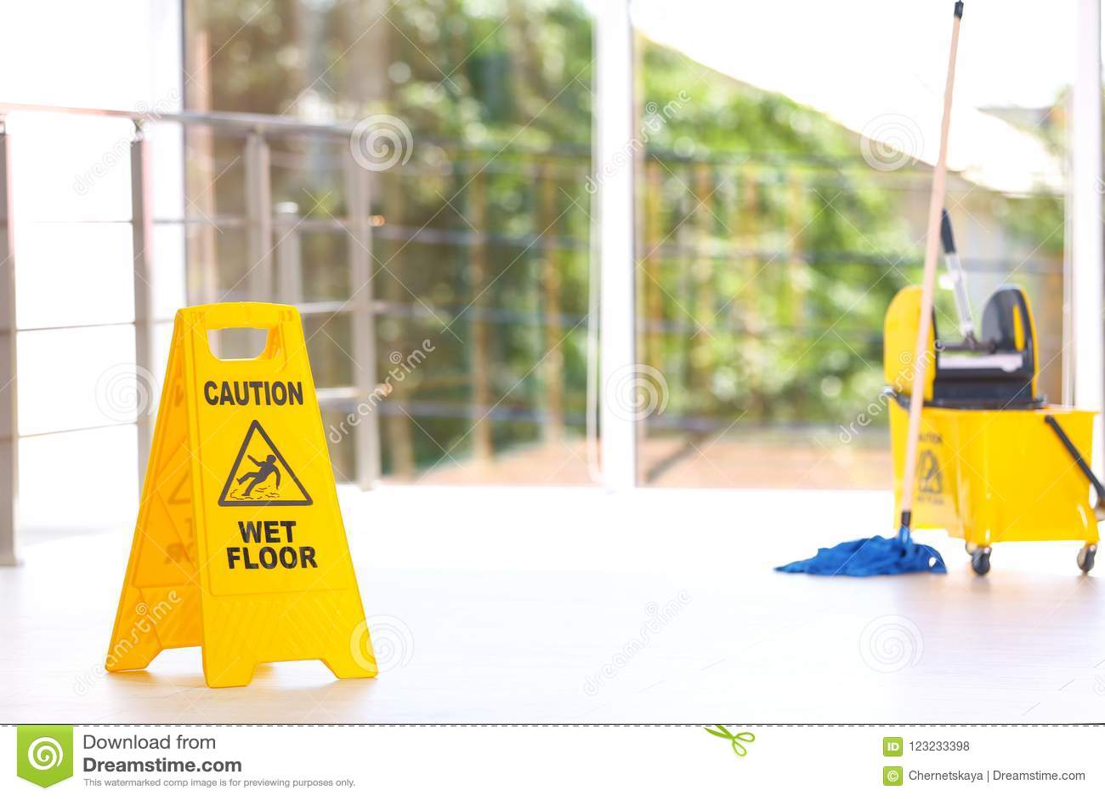 Sinal de segurança com a cubeta molhada do espanador do assoalho do cuidado da frase, dentro serviço da limpeza