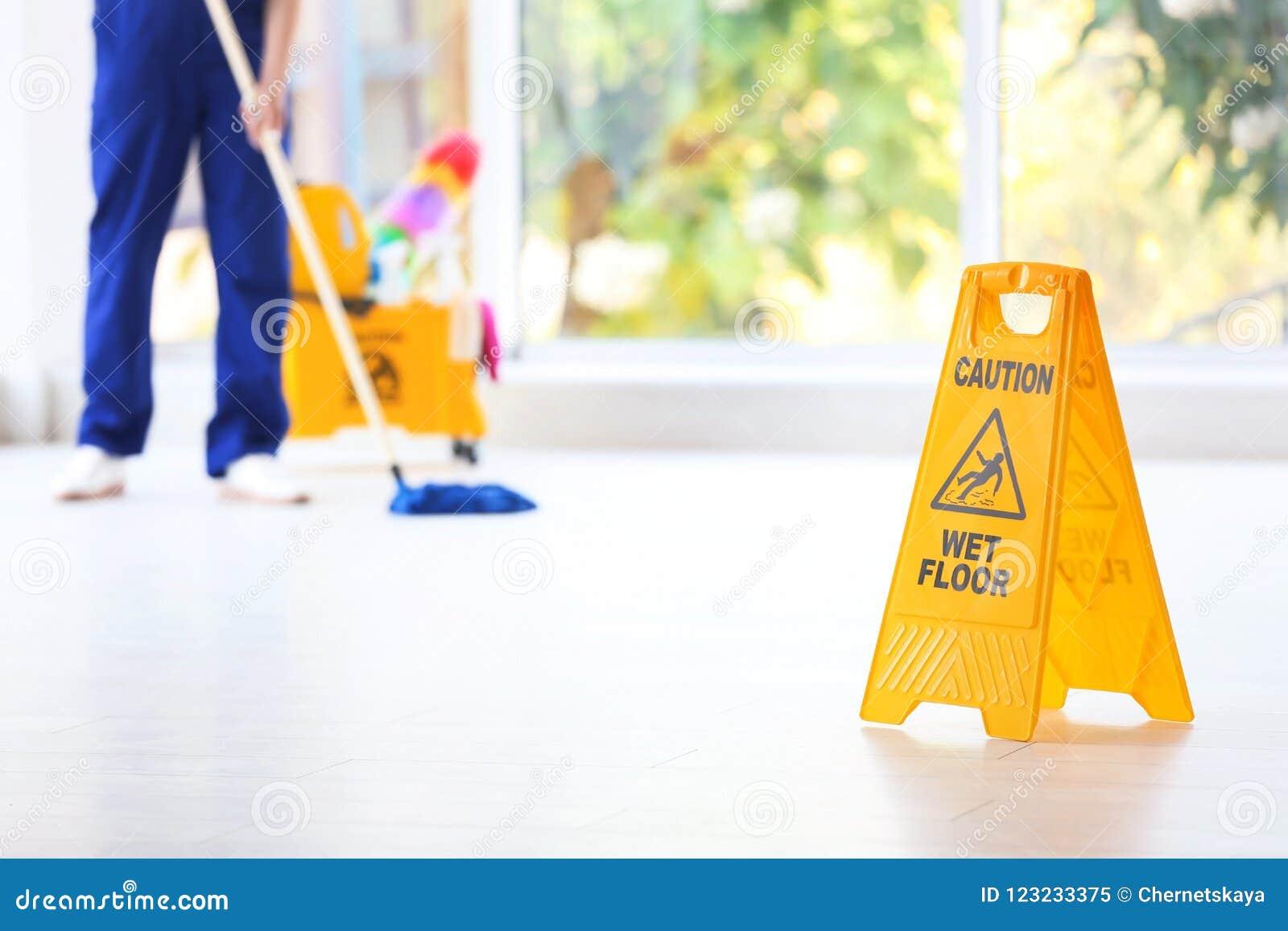 Sinal de segurança com o assoalho molhado do cuidado da frase