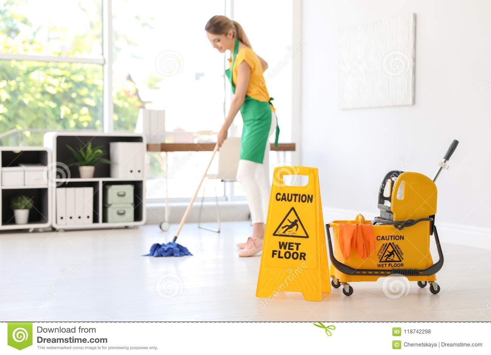 Sinal de segurança, cubeta do espanador com fontes de limpeza e jovem mulher no fundo