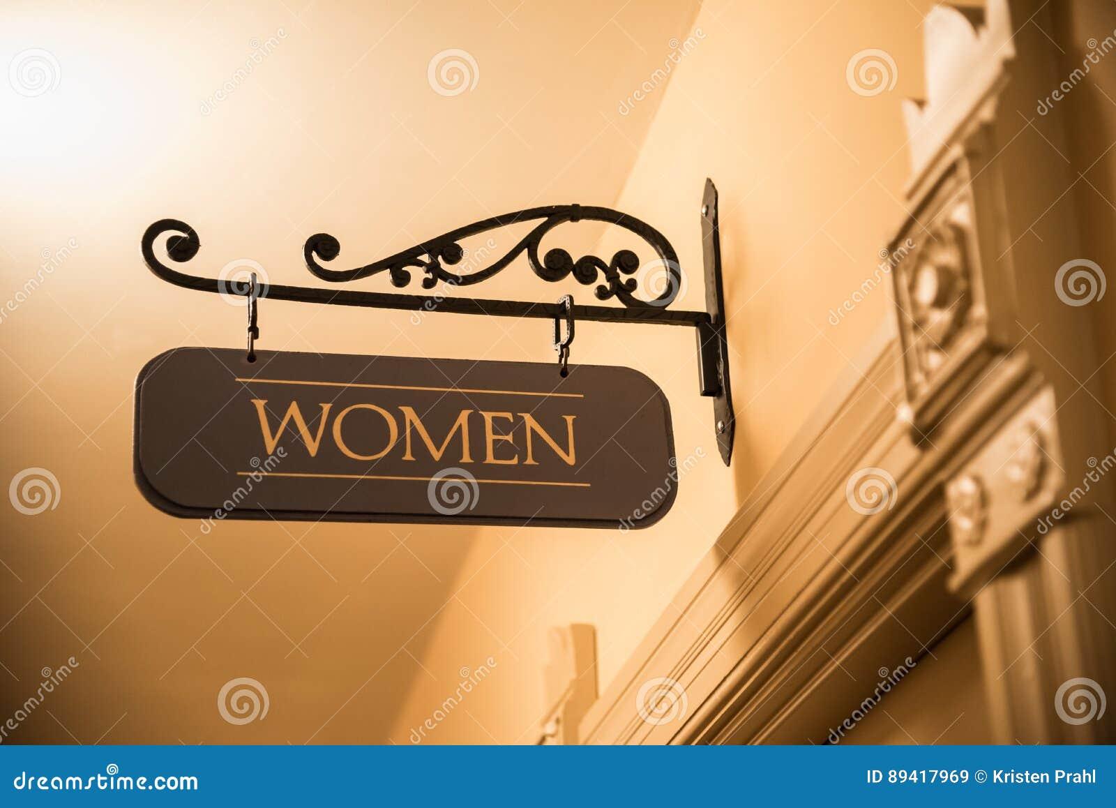 Sinal do banheiro de mulheres extravagantes que pendura acima da porta