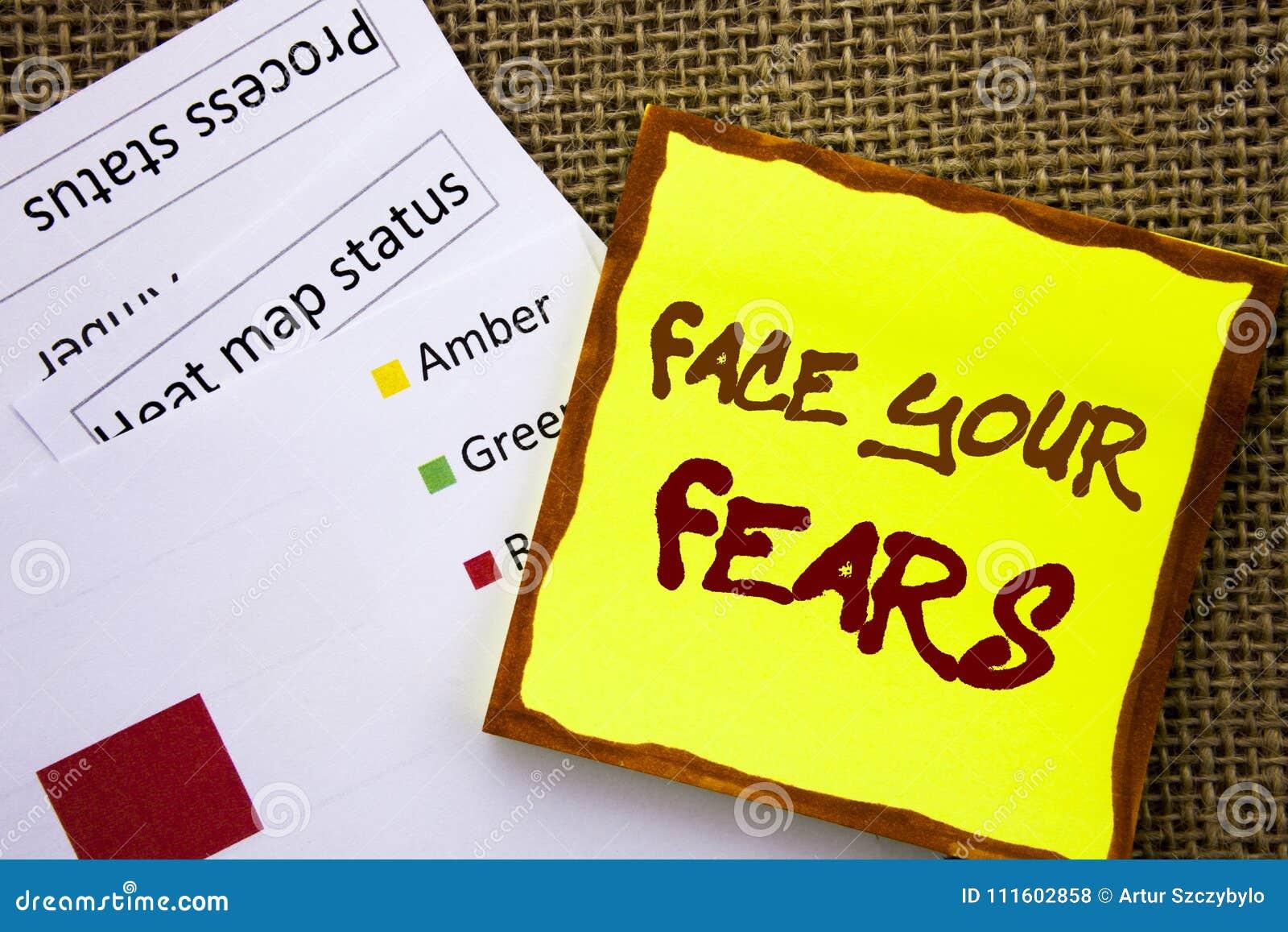 Sinal escrito à mão do texto que mostra a cara seus medos Conceito do negócio para a bravura corajoso da confiança de Fourage do