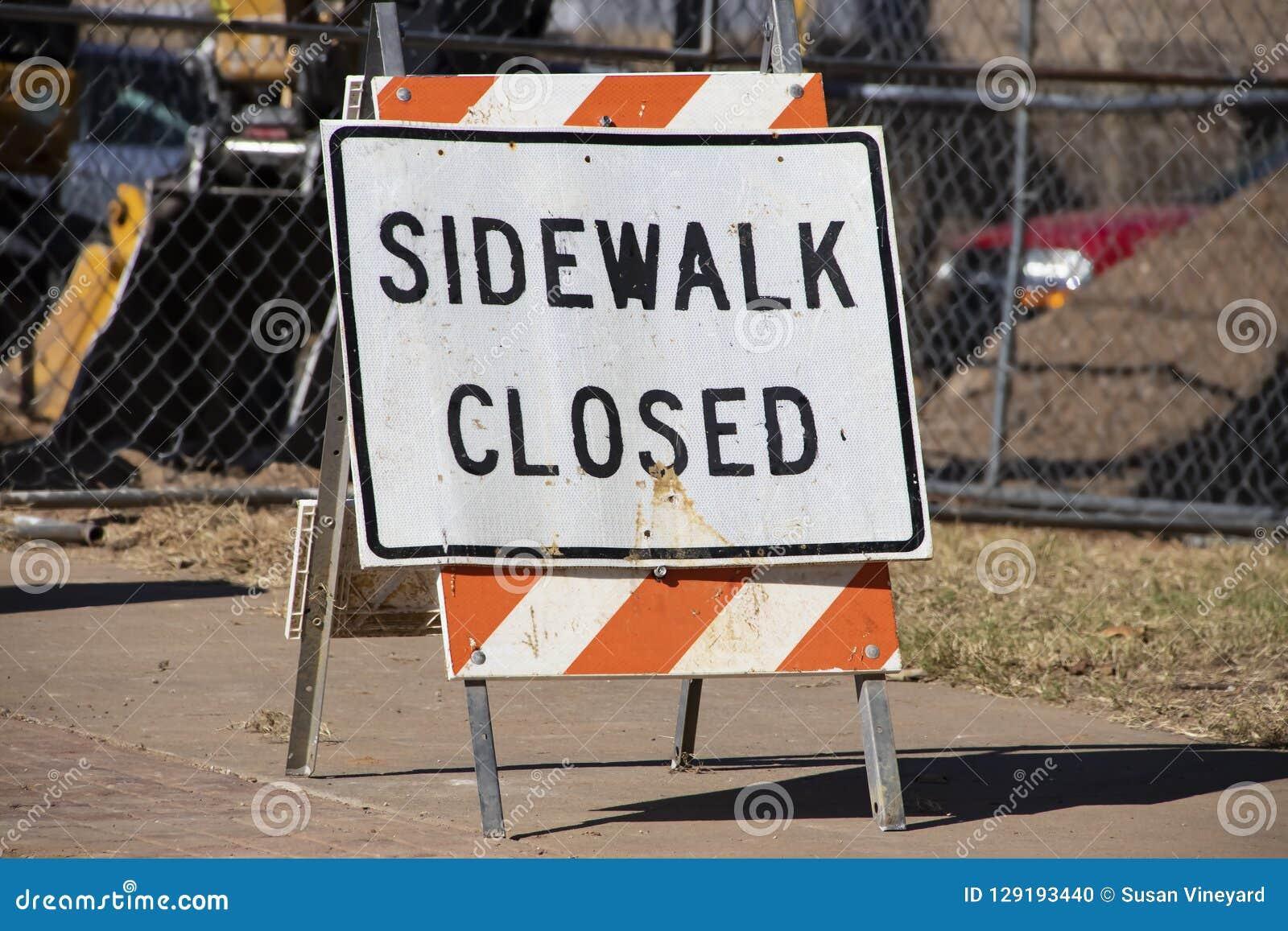 Sinal estando Closed do passeio no passeio na frente da cerca e do equipamento de construção borrados no fundo