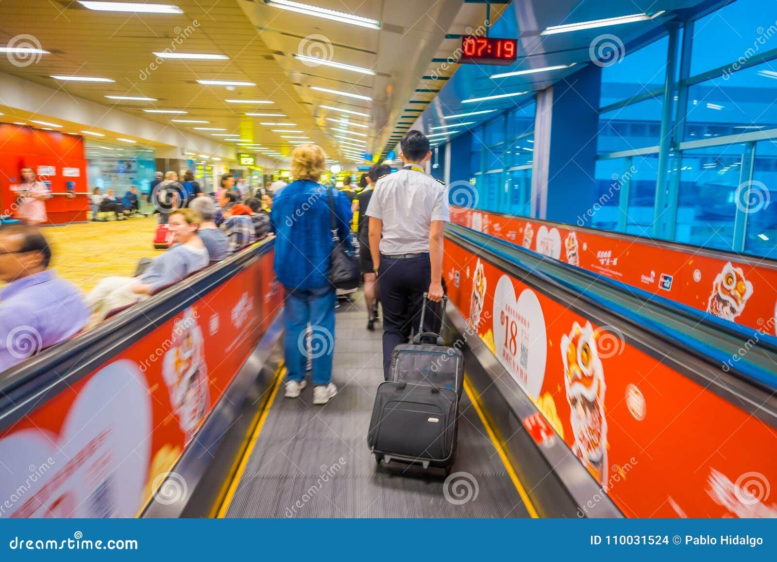 SINGAPORE, SINGAPORE - JANUARI 30, 2018: Niet geïdentificeerde mensen die bij roltrappen bij Changi Internationale Luchthaven bin