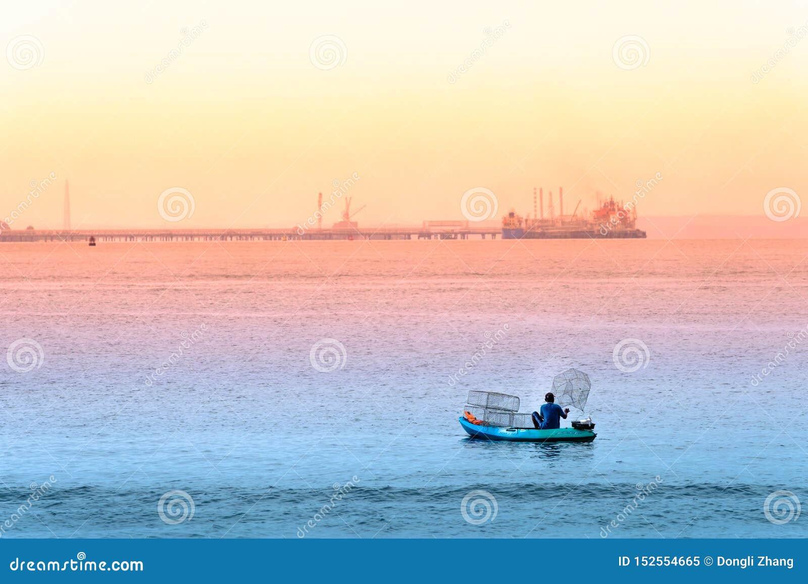 Singapore-29 JUNI 2019: Fiskaren fiskar i havet, genom att förlägga burar