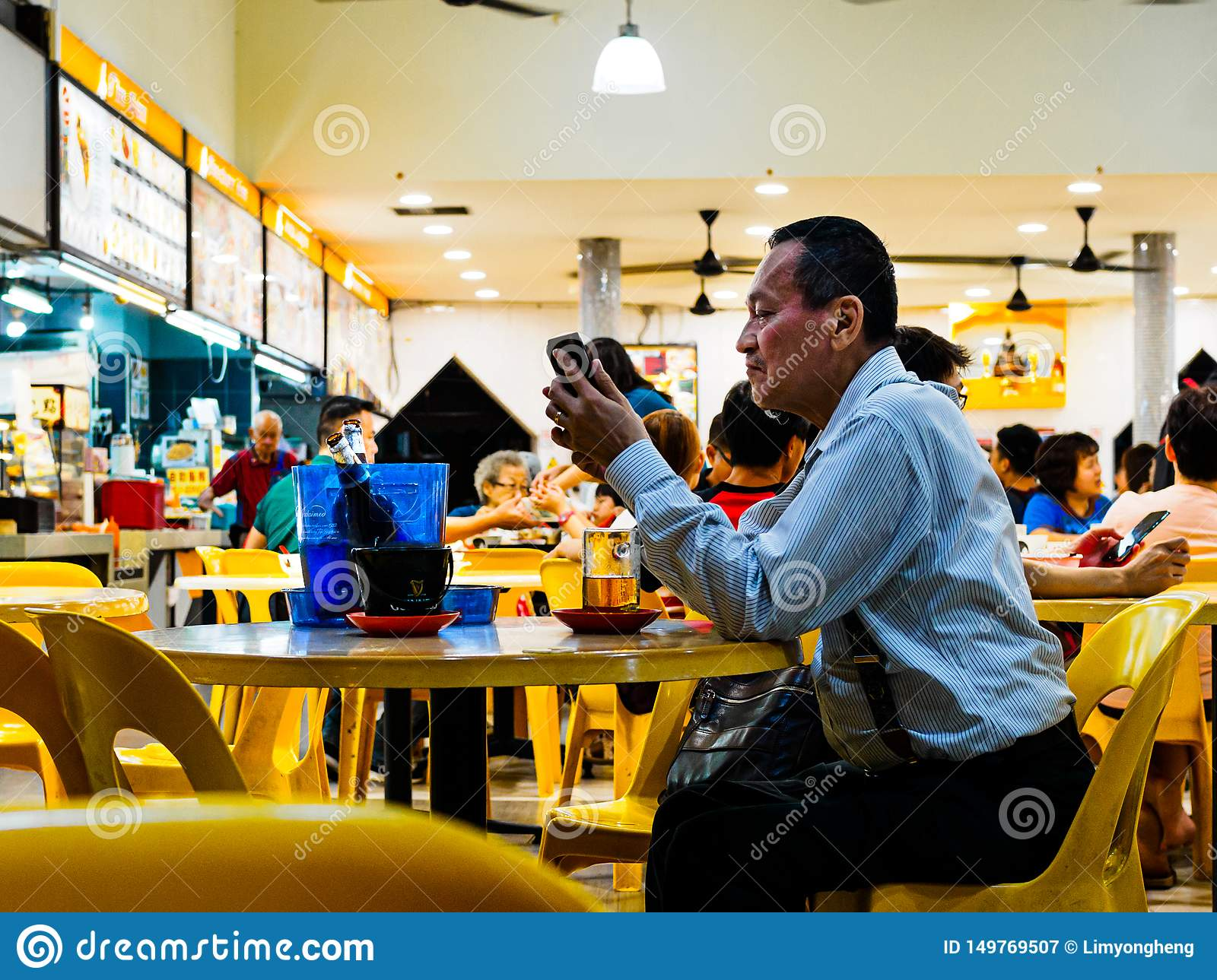 SINGAPORE - 17 MAR 2019 - A middle aged man in office atire enjoys a late night beer at an eatery / coffeeshop / kopitiam, /
