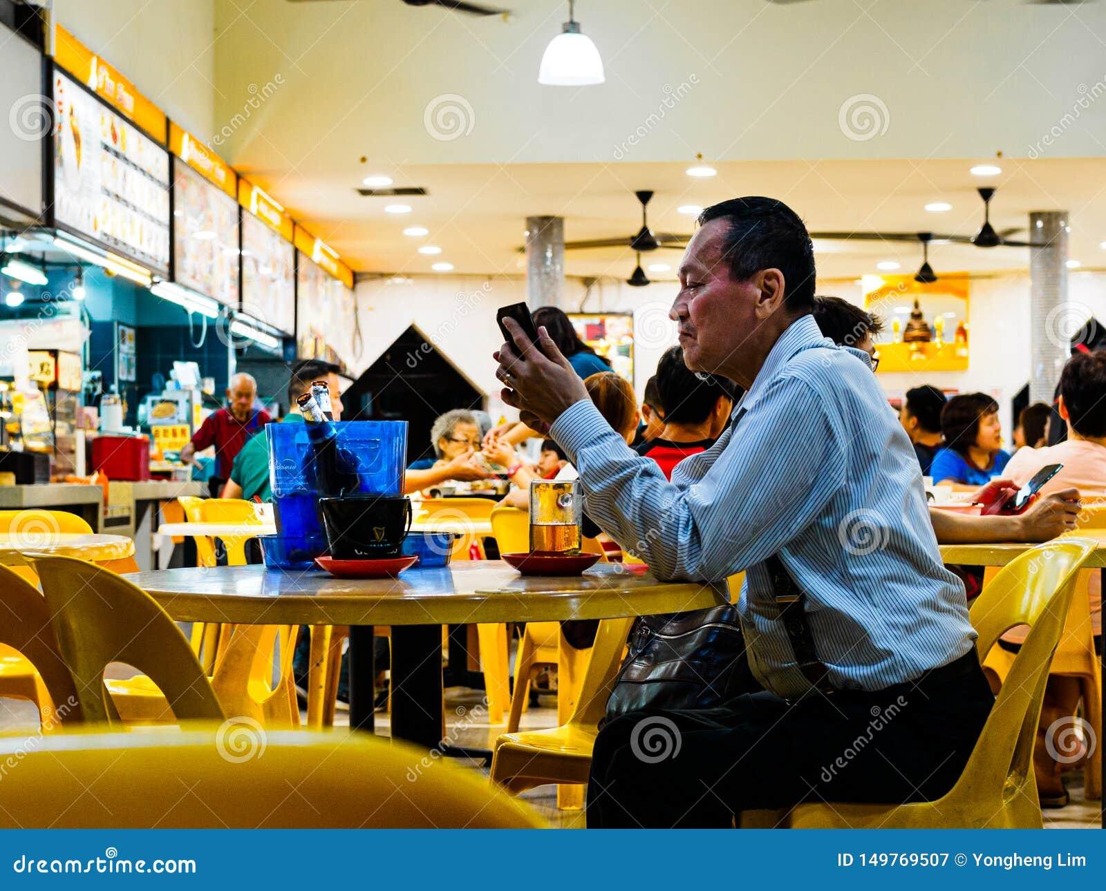 SINGAPORE - 17 MARZO 2019 - un uomo invecchiato medio nel atire dell ufficio gode di una birra a tarda notte ad un ristorante/kop