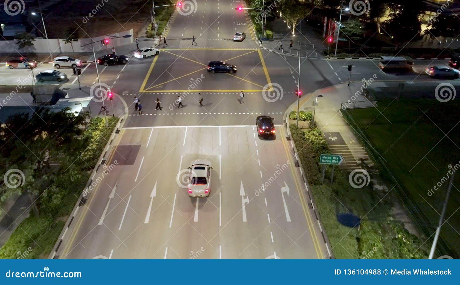 Singapore - 25 September 2018: Hoogste Weergeven van straat met kruisingsweg en mensen die de straat kruisen bij nacht schot