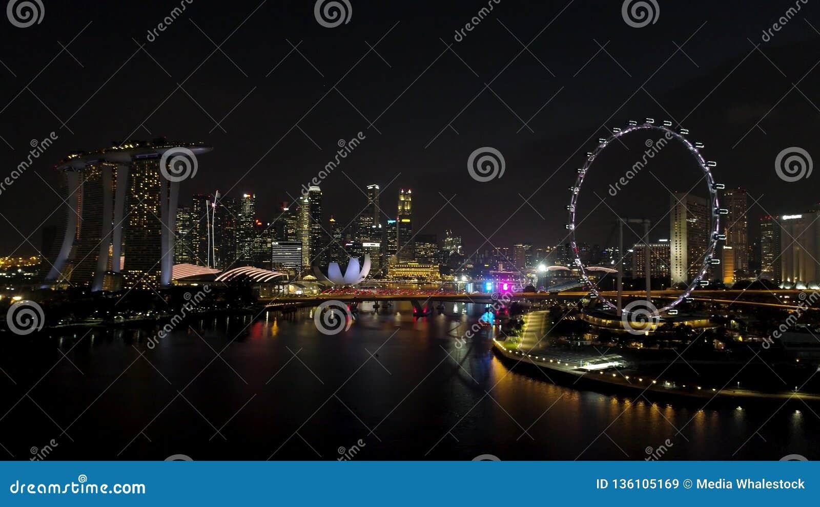 Singapur - 25 de septiembre de 2018: Vista aérea de la ciudad grande con muchas luces, cielo nublado, y noria en la noche tiro