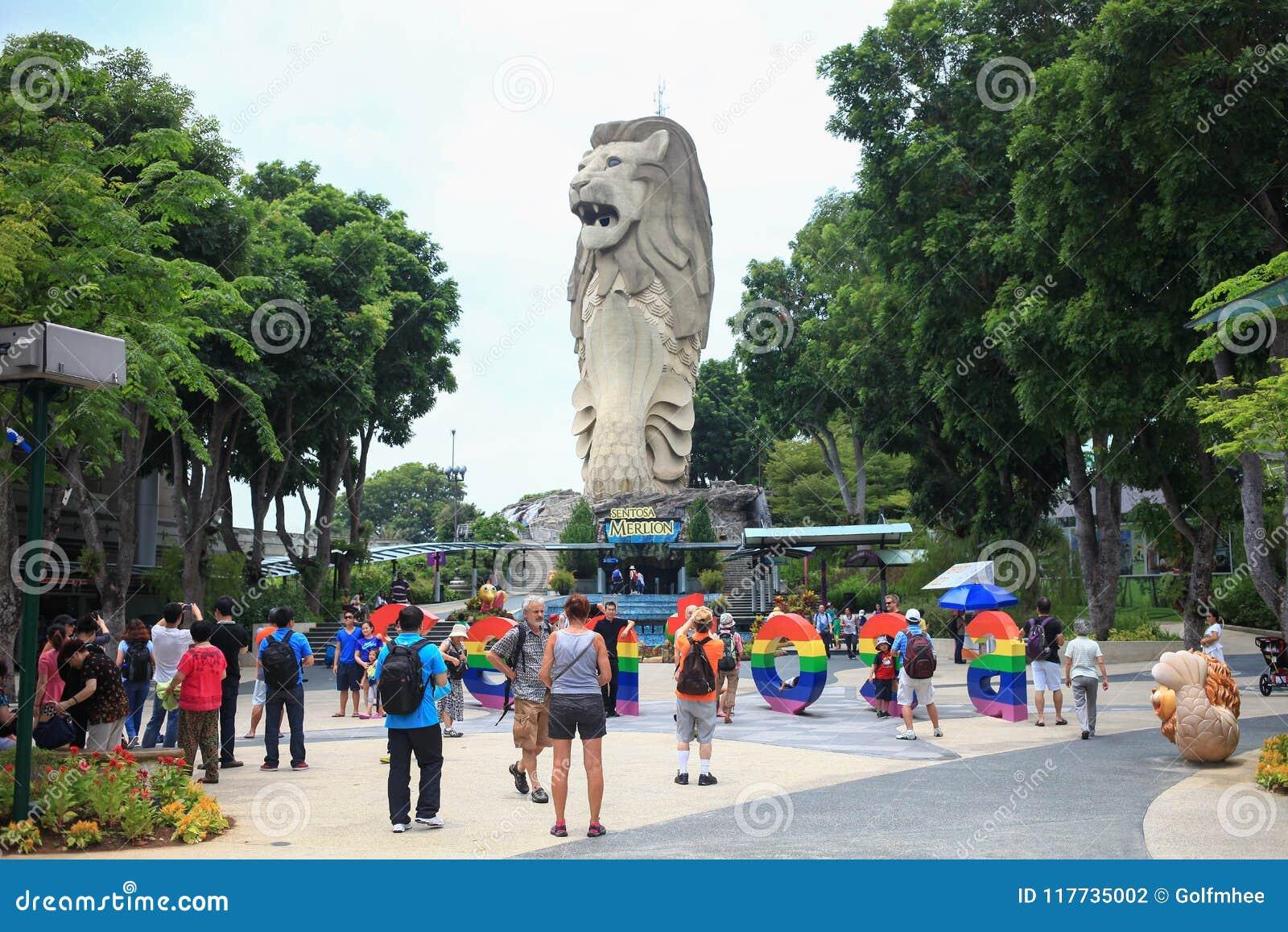 SINGAPUR - 26 Marzec, 2014: Podróży ludzie biorą fotografie Merlion